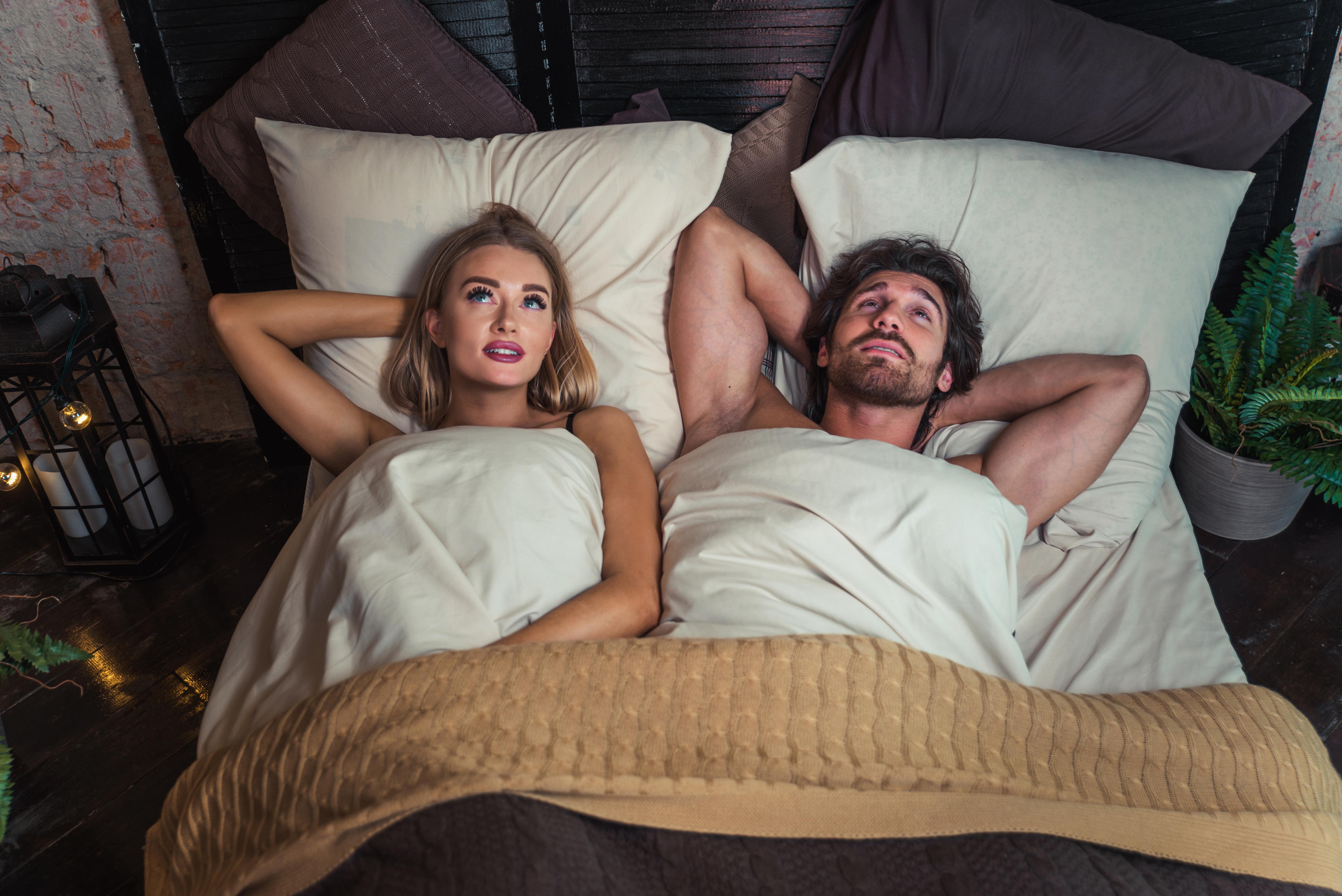 Pareja en la cama tras un encuentro sexual satisfactorio