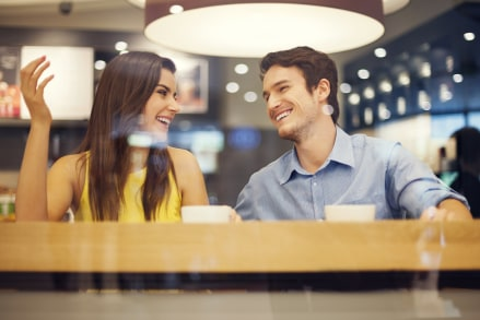 pareja tomando un café y riéndose juntos