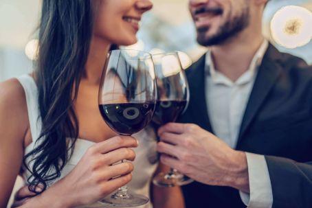pareja durante su primera cita brindando con una copa de vino