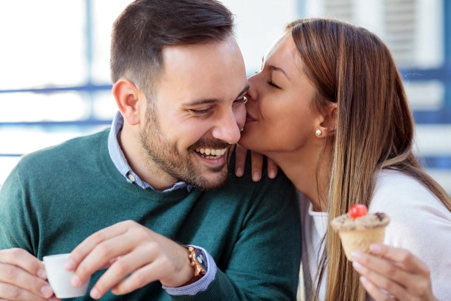 pareja feliz comiendo helado y dándose un beso en la mejilla