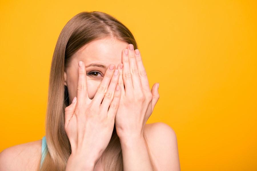 mujer tímida tapándose la cara mientras piensa frases para ligar con un chico
