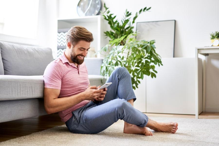 chico con móvil en la mano busca contactos gay para ligar online
