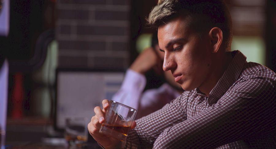 hombre mirando a un vaso preguntándose cómo conseguir novia