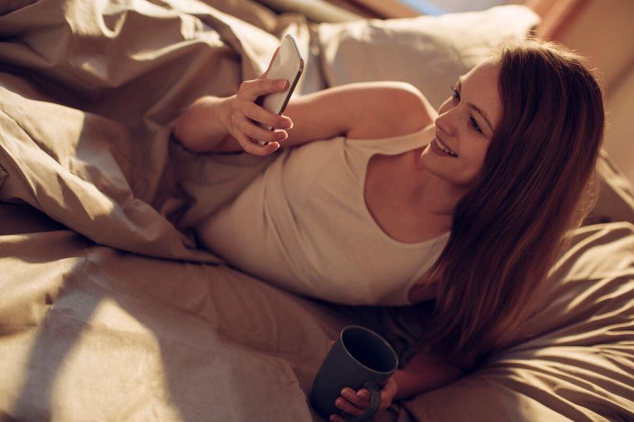 Mujer en la cama mirando en su móvil aplicaciones para ligar
