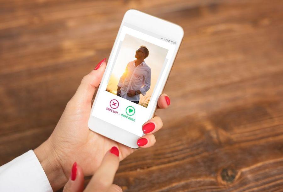 Mano de mujer con app para ligar en la pantalla del móvil