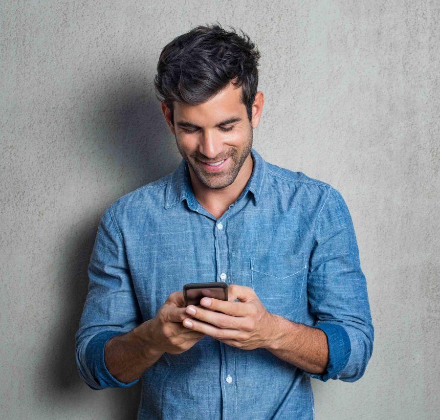 hombre sonriente consulta app para buscar pareja