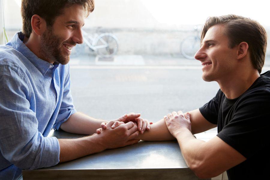 pareja gay cogida de la mano en un cita
