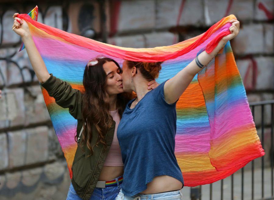 pareja mujeres lesbianas besándose bajo la bandera lgbt