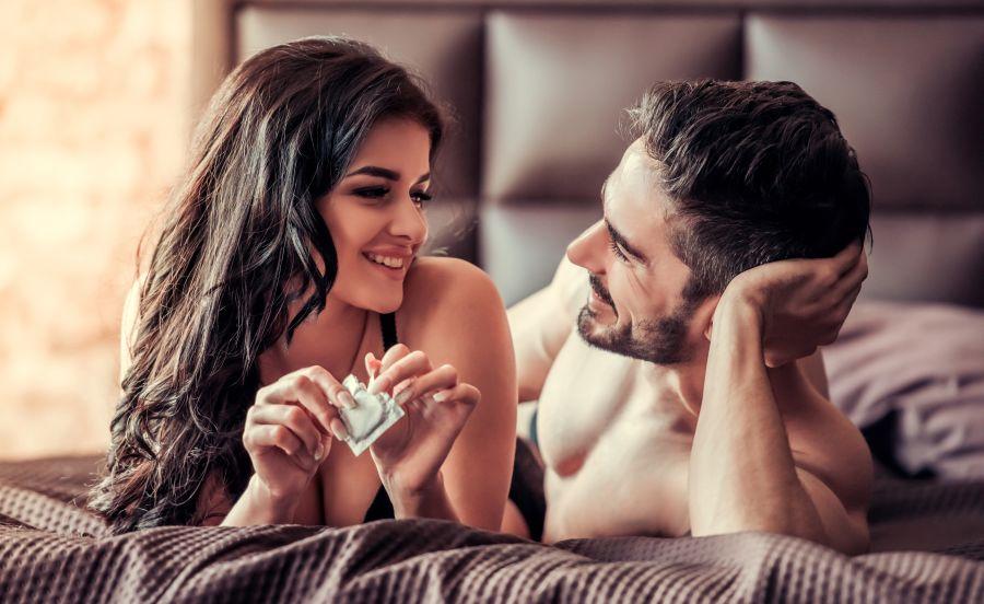 pareja en la cama con condón teniendo contactos eróticos